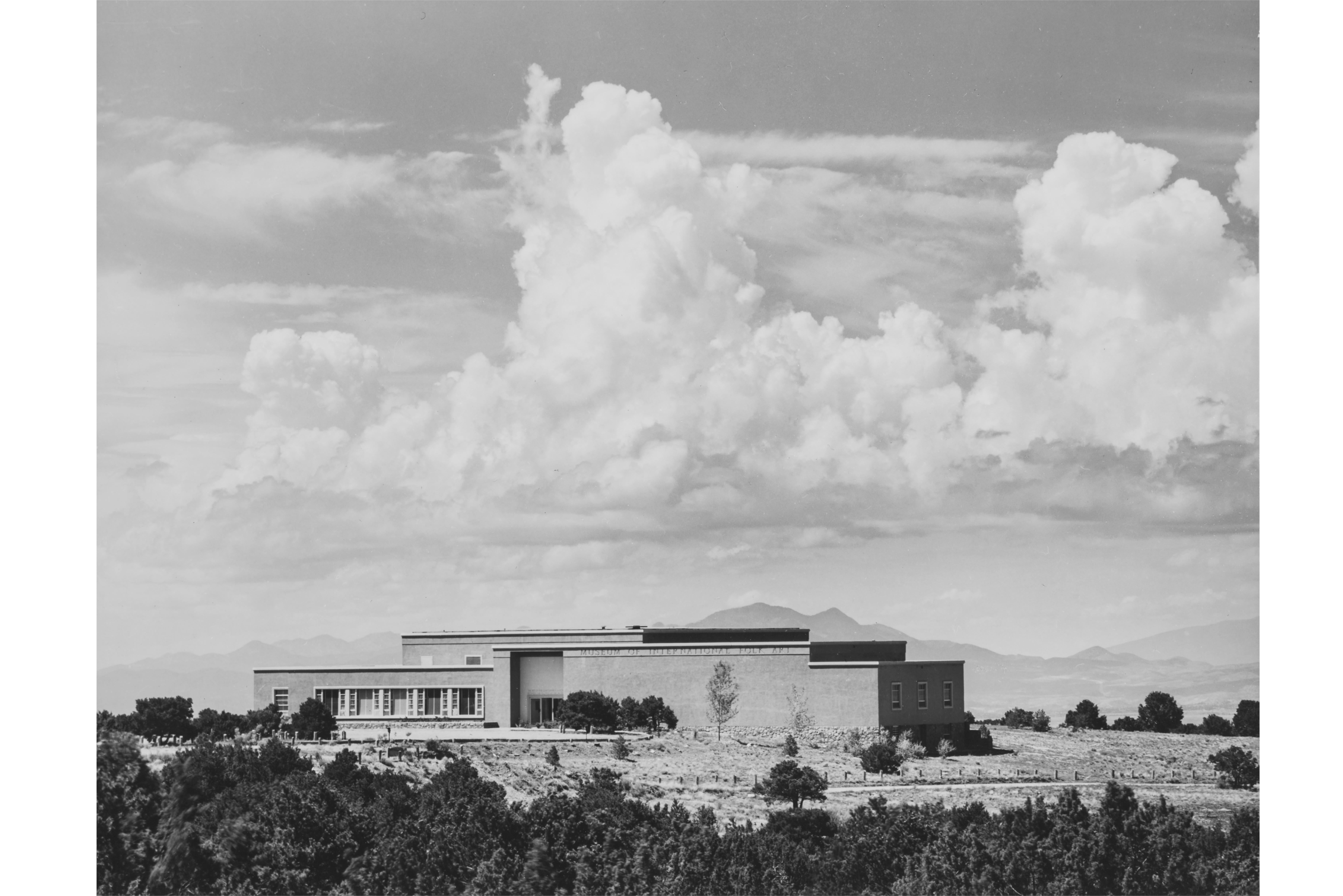 image of the Museum exterior, showing it settled into the landscape under a dramatic cloudbank